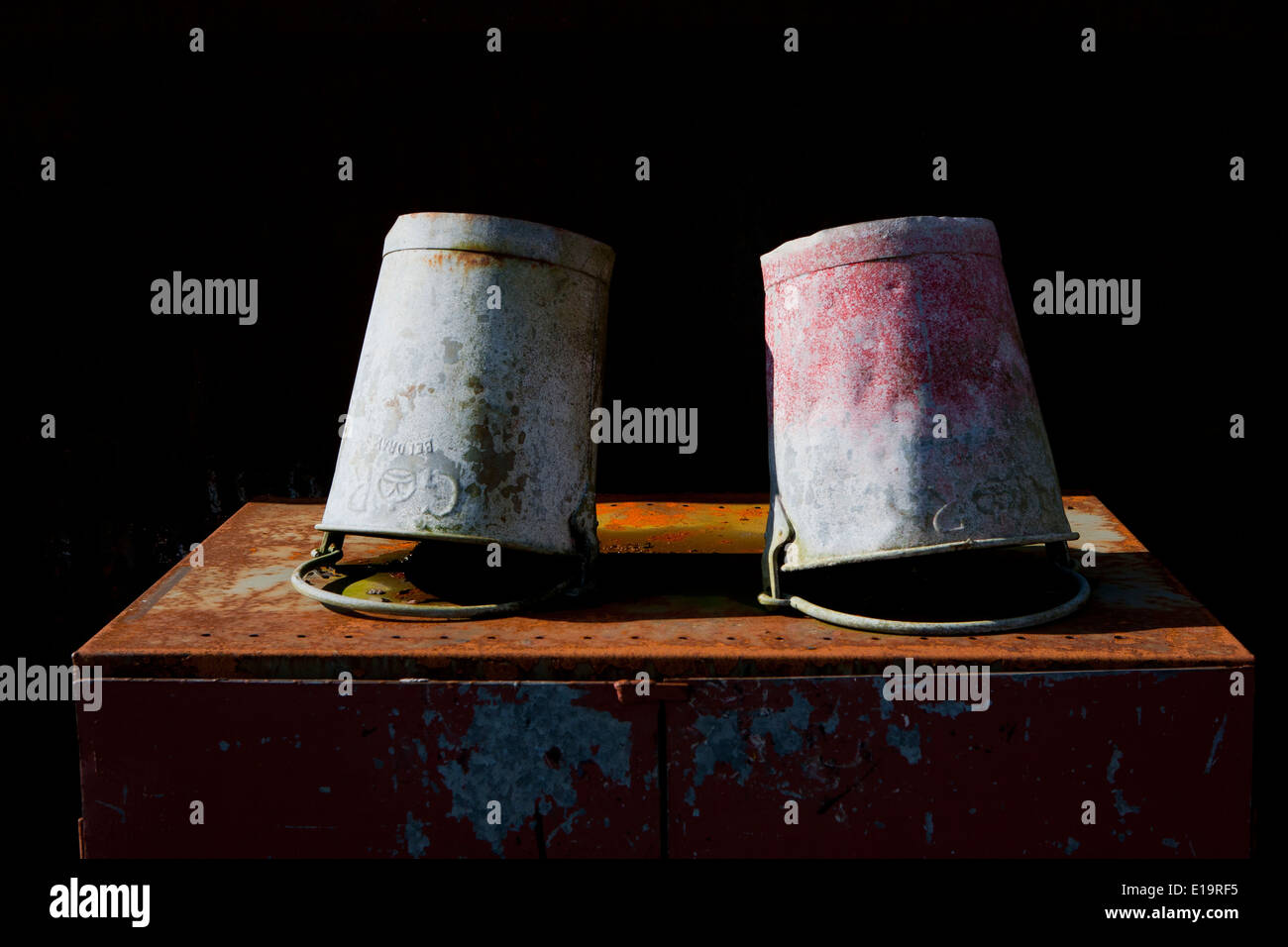 Two galvanized buckets with faded paint resting upside down on rusty metal. - Stock Image