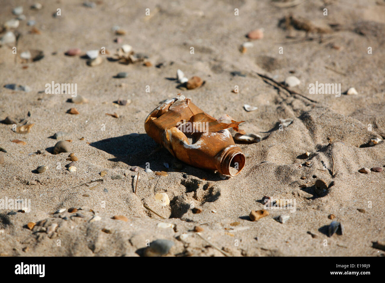A plastic bottle washed up on a beach as rubbish. - Stock Image