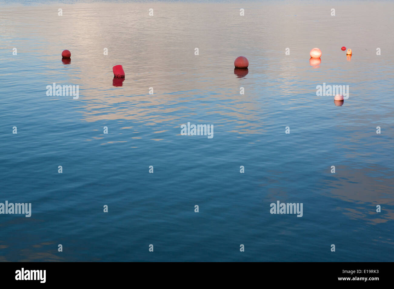 Cloudy sky reflected in the sea, bouys floating. - Stock Image