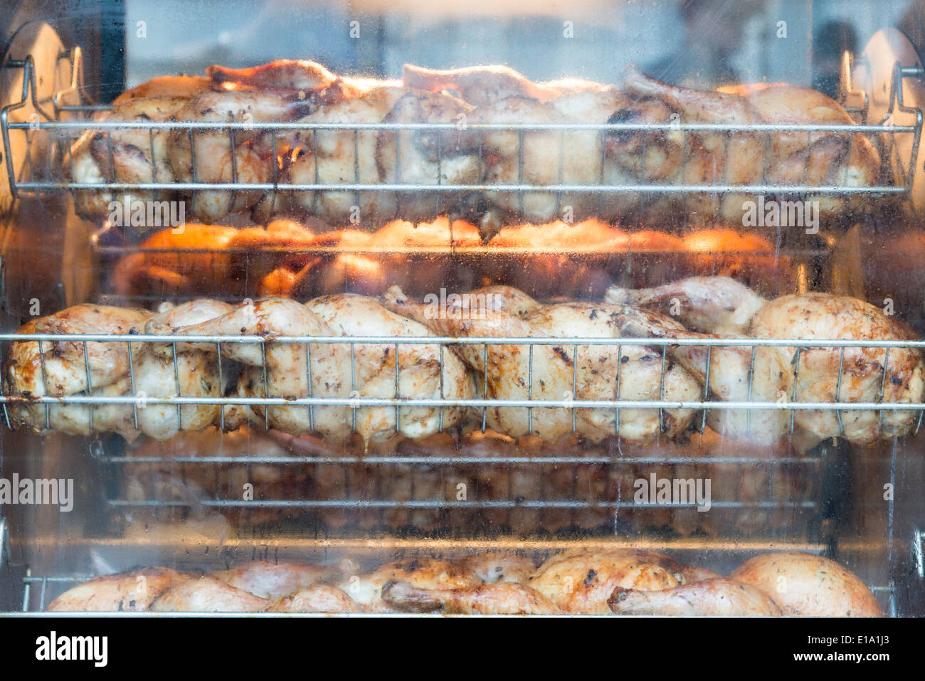 Chickens roasting in a rotisserie - Stock Image