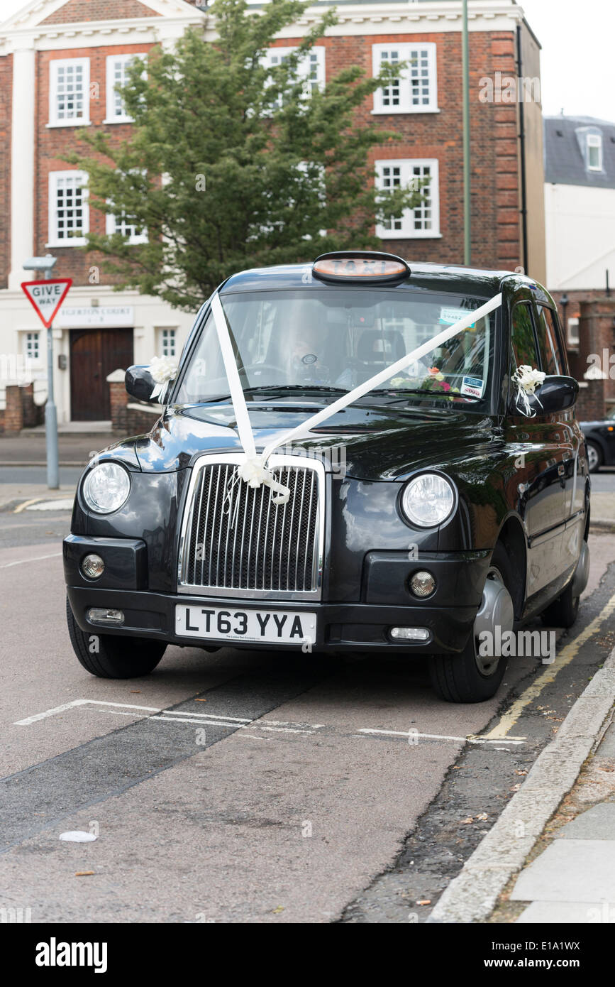 A black cab London taxi with decorative white wedding ribbons attached waiting outside a wedding venue. - Stock Image