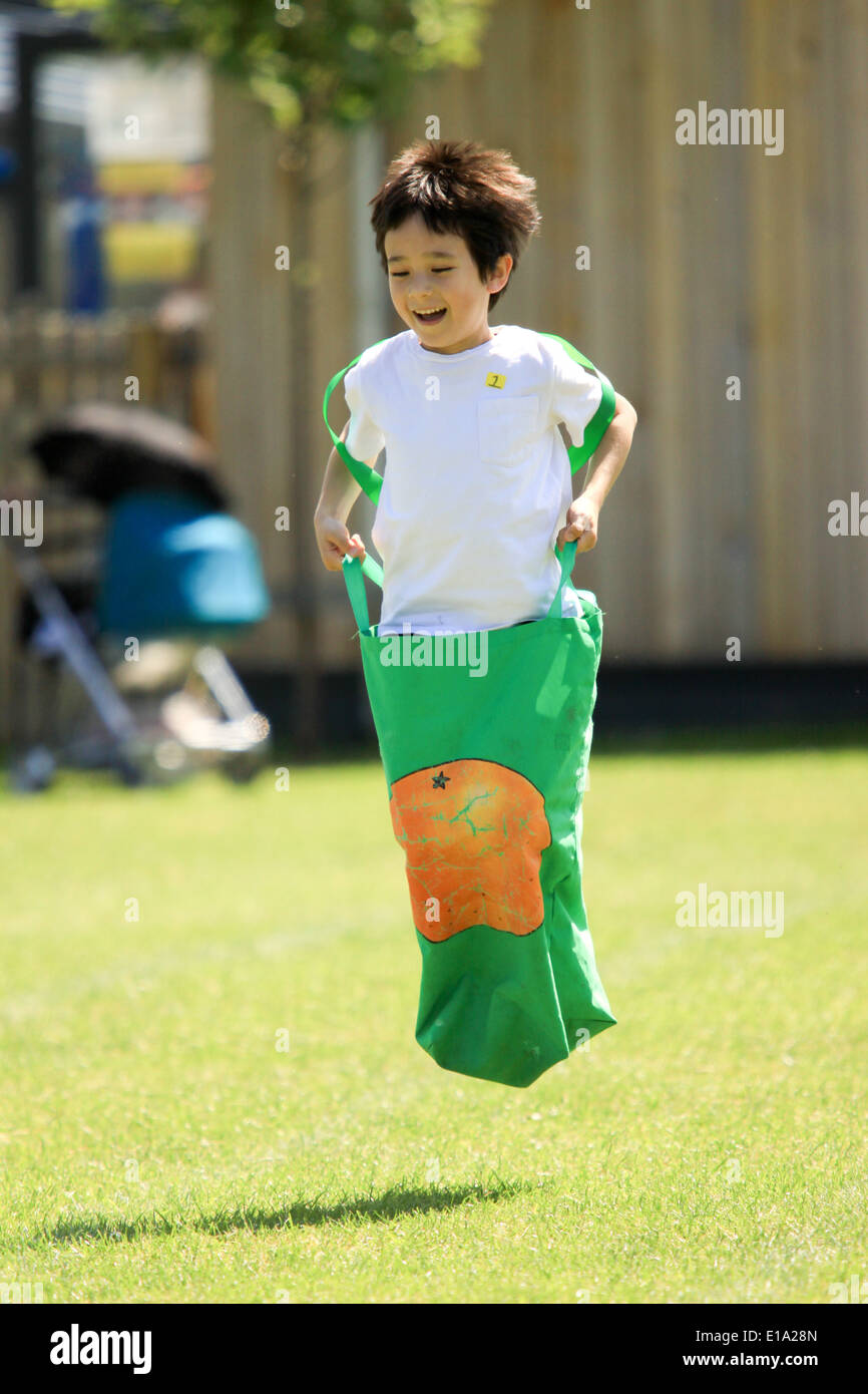 Young boy competing in sack race on sportsday - Stock Image