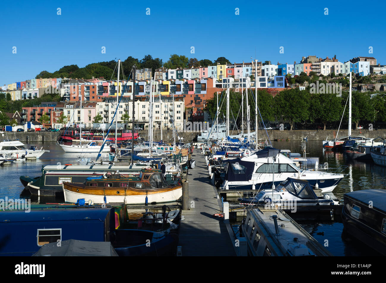 Boats moored in Bristol harbour, UK, with colourful Cliftonwood houses on the hillside in the background - Stock Image