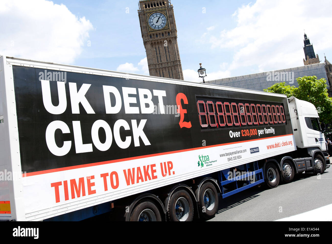 UK Debt Clock passes the Houses of Parliament in London on 22.06.2010. - Stock Image