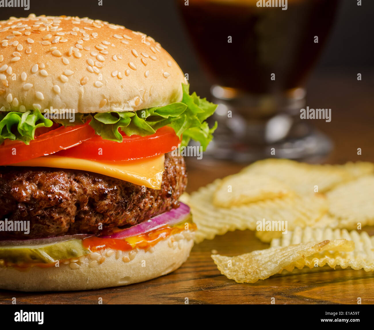 A deluxe cheeseburger with potato chips and cola. - Stock Image