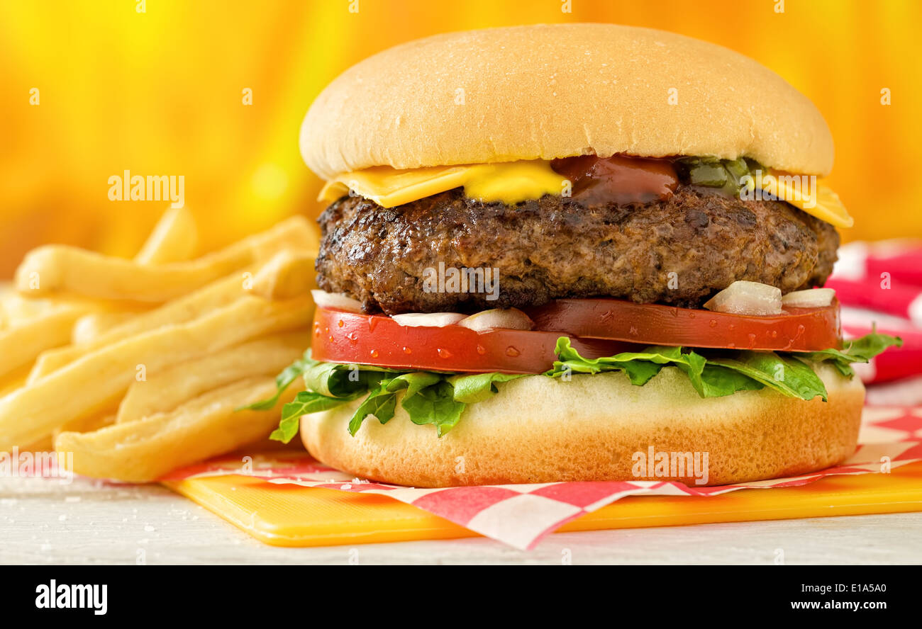 A classic style cheeseburger with beef, cheese, lettuce, tomatoe, onion, mustard, ketchup, and relish with french fries. - Stock Image