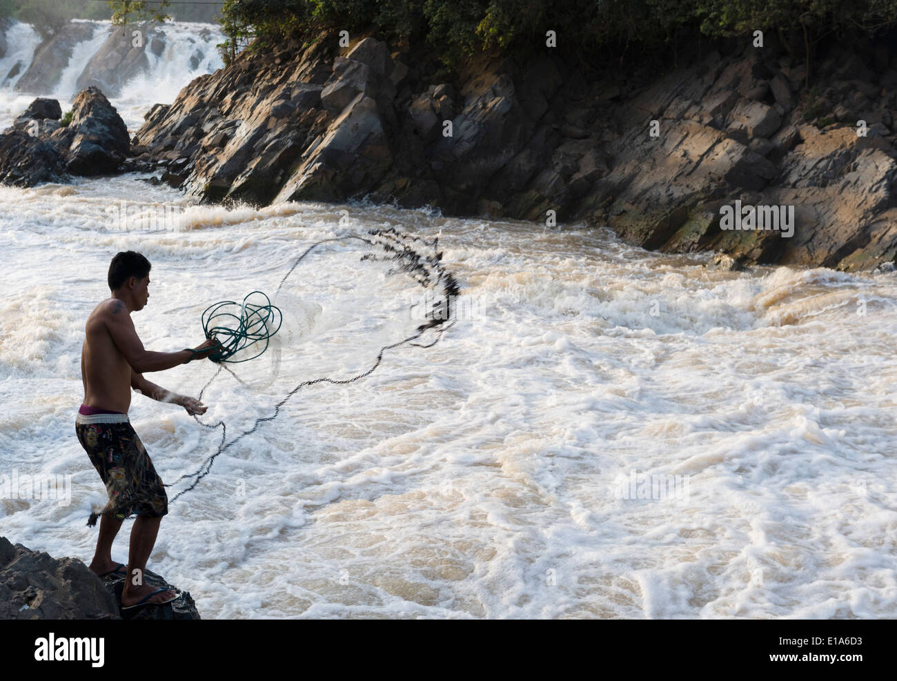 Net fishing at the Khone Phapheng Falls, Mekong River,, Champasak, Laos. Fisherman is Saimoun from Ban Takho Village, 28 years. - Stock Image