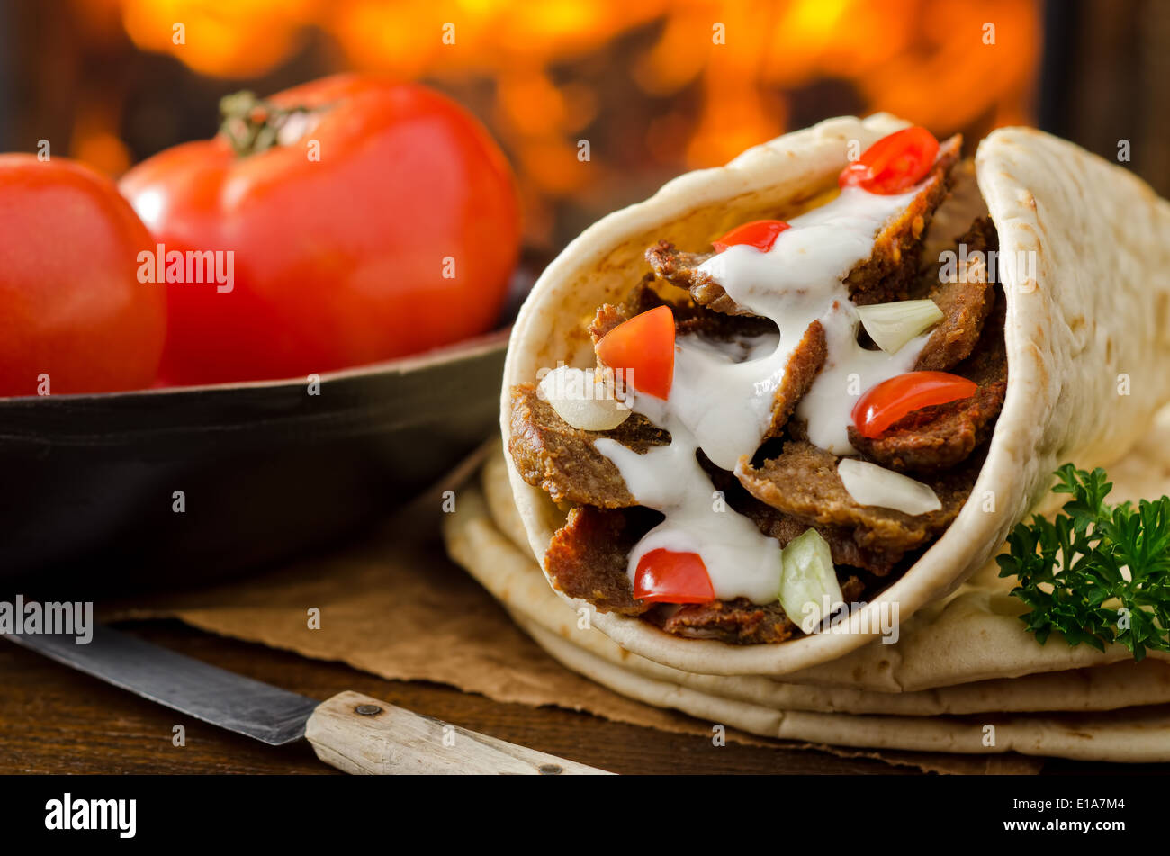 A gyro donair with onion and tomato against a hardwood fire background. - Stock Image