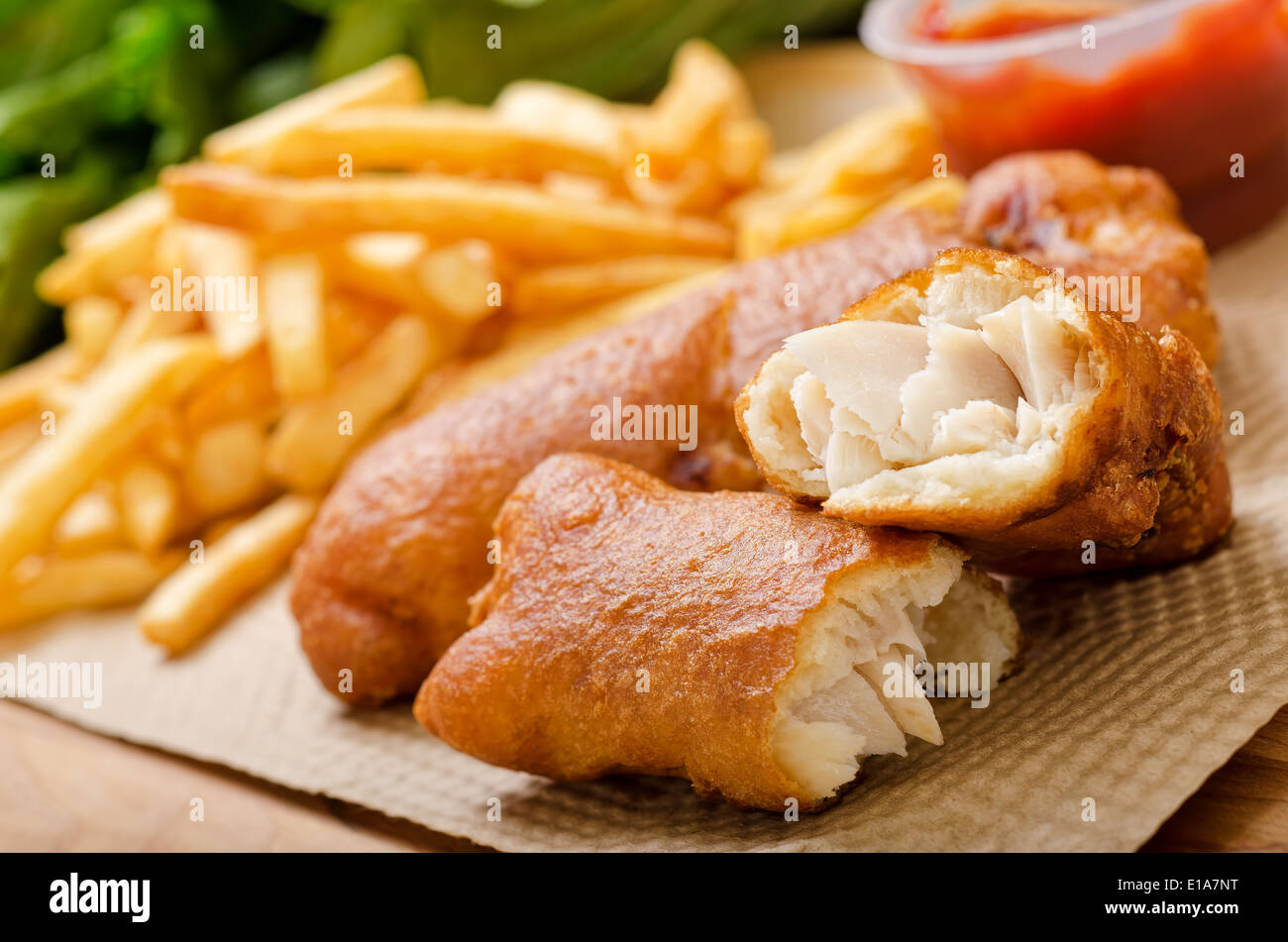A delicious crispy battered deep fried fish and chips with greens and ketchup. - Stock Image