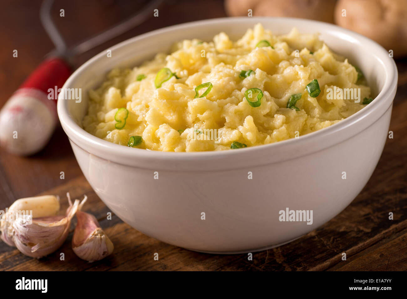 A bowl of delicious creamy garlic mashed potatoes with butter and green onions. - Stock Image