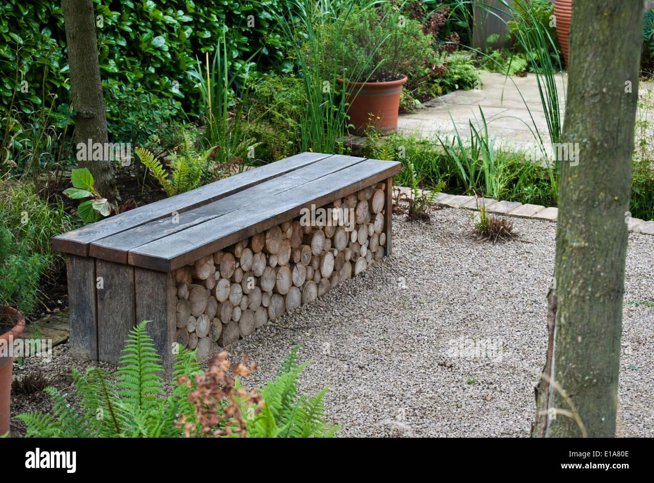 Ornate Garden Bench Doubling As A Log Store   Stock Image