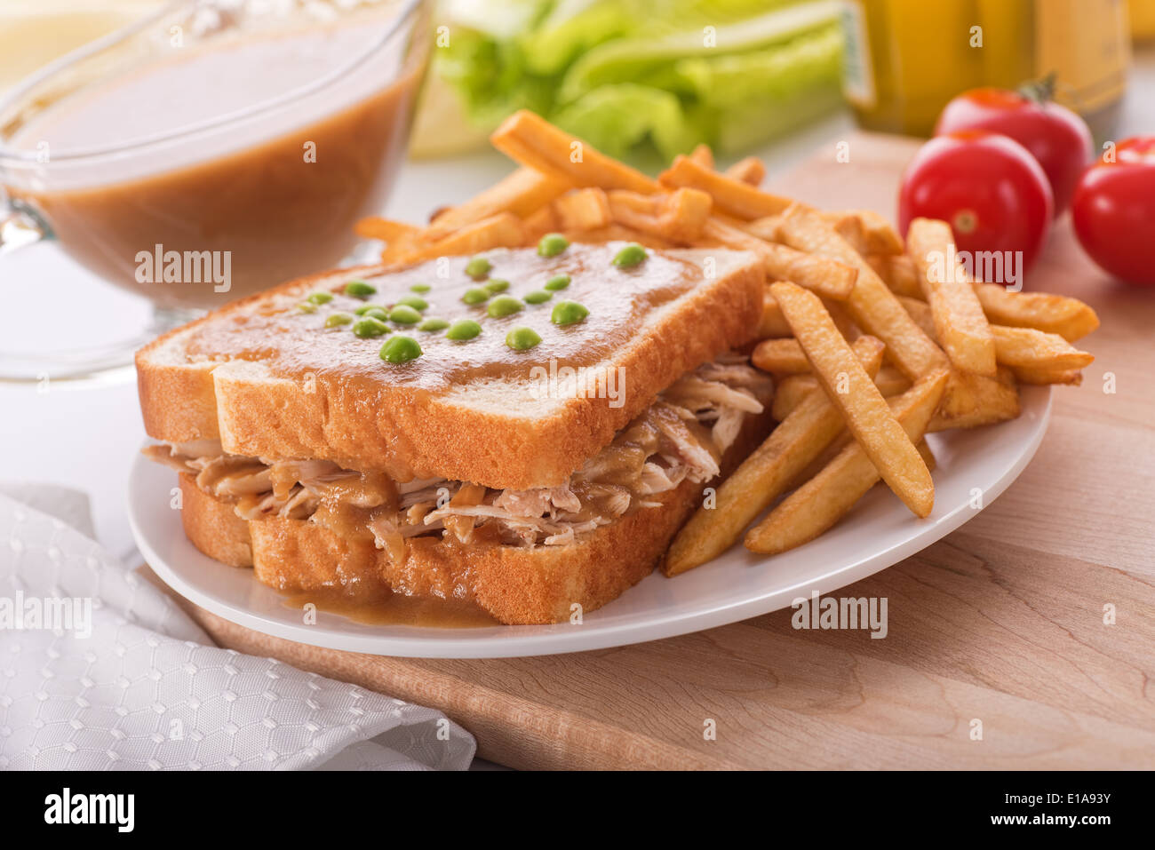 A delicious hot turkey sandwich with gravy, green peas, and french fries. - Stock Image