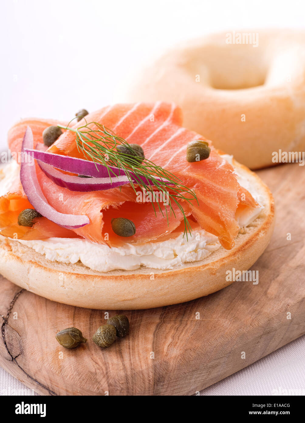 A delicious bagel with smoked salmon lox, cream cheese, red onion, capers, and a sprig of dill. - Stock Image