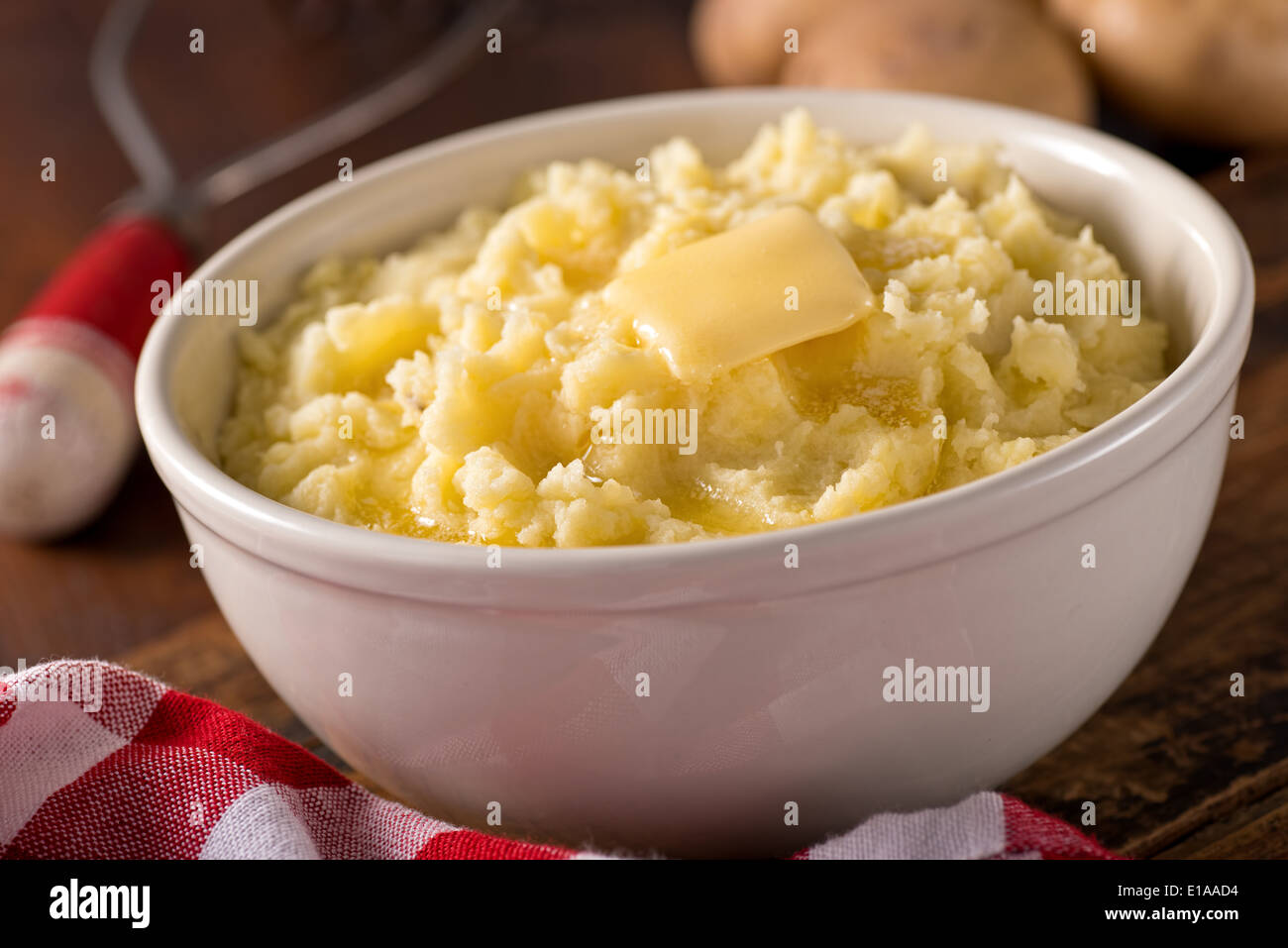 A bowl of creamy delicious mashed potatoes with melted butter. Stock Photo