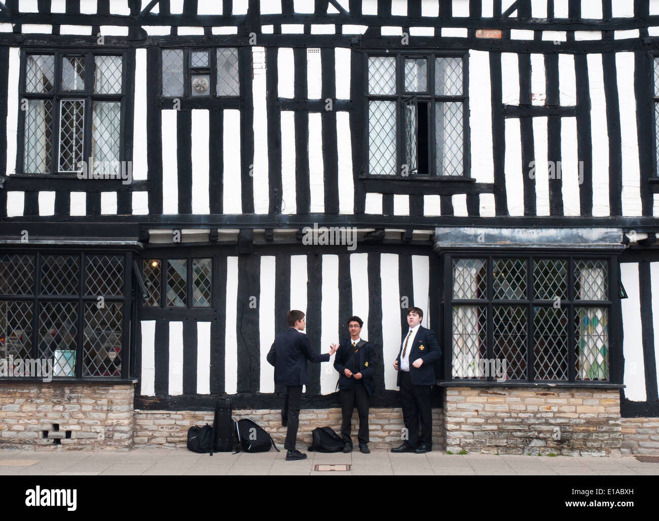 Schoolboys outside the Tudor-style half-timbered Falcon Hotel in Stratford-upon-Avon, England - Stock Image