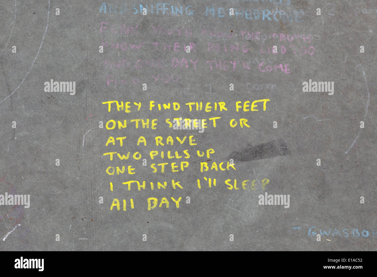 They find their feet on the street at a rave two pills up and one step back i think i'll sleep all day Message on Pavement - Stock Image