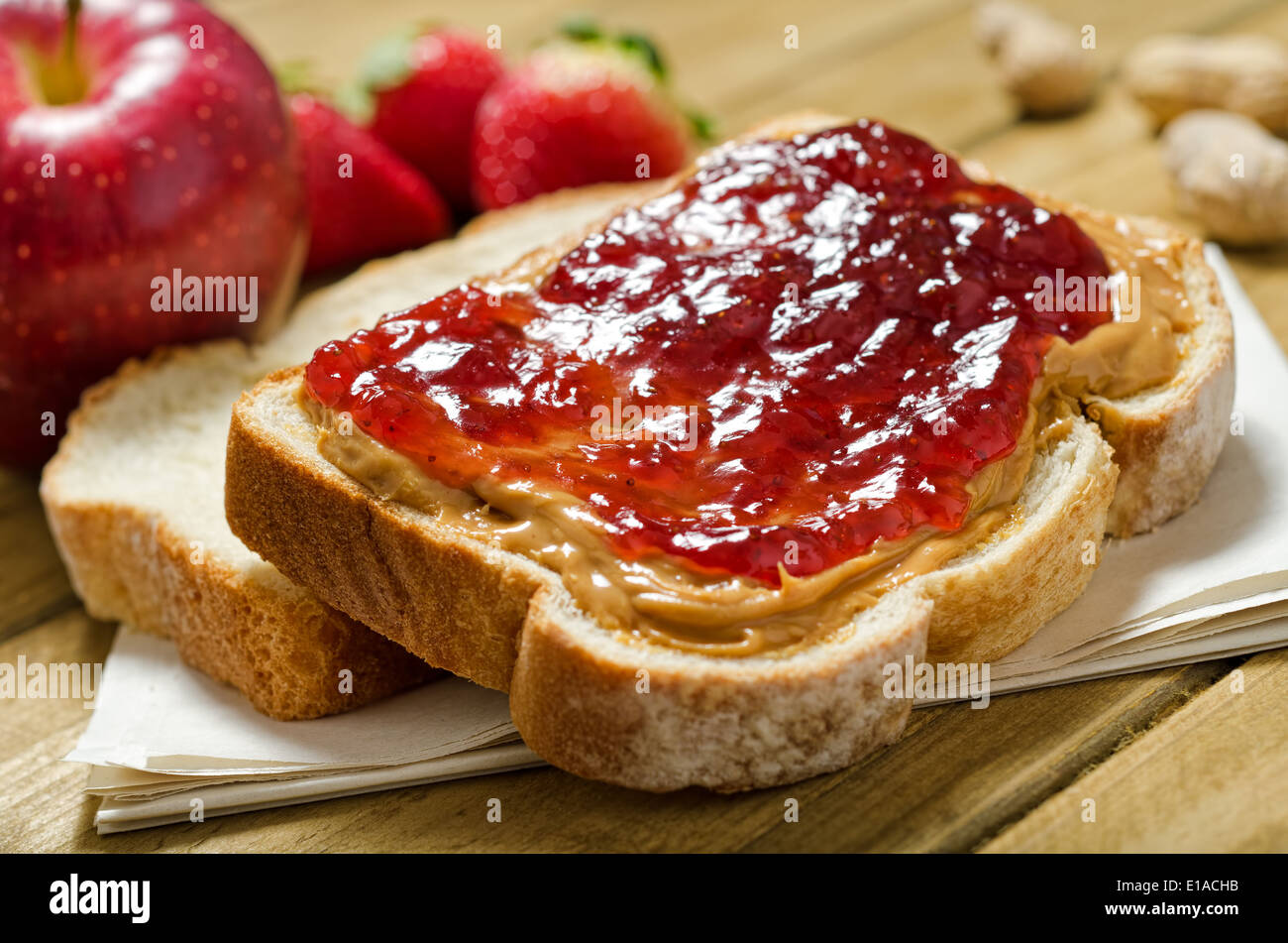 A nutritious peanut butter and jelly sandwich with apples, strawberries, and peanuts. - Stock Image