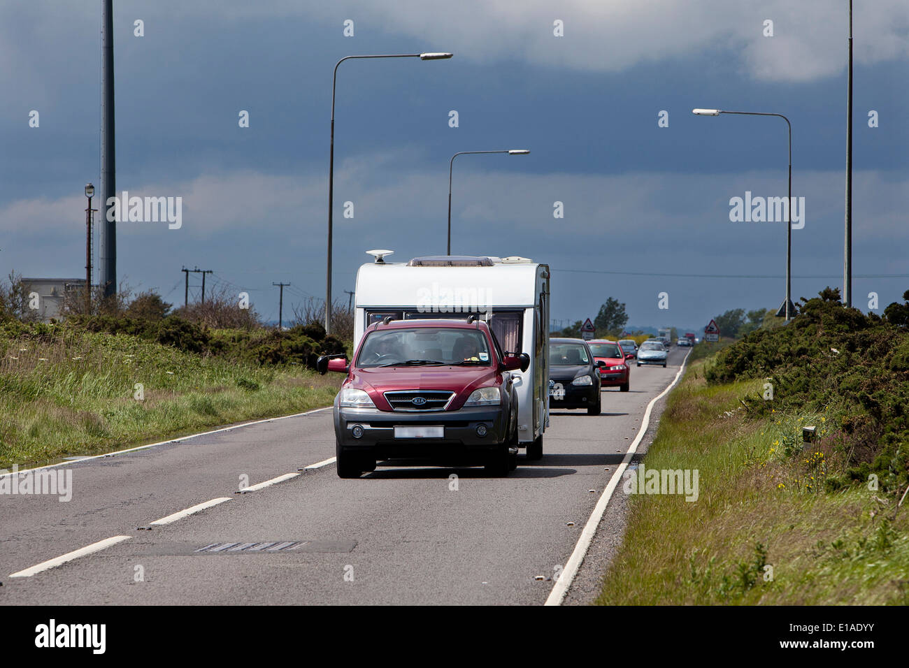 Motorists driving up the A47 Acle Straight to Great Yarmouth as storm clouds gather in the west - Stock Image