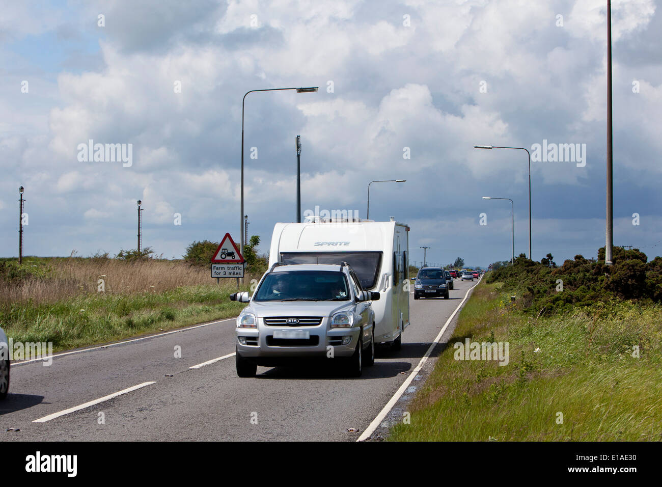 Caravaners driving up the Acle Straight to Great Yarmouth as dark storm clouds approach from the west. - Stock Image