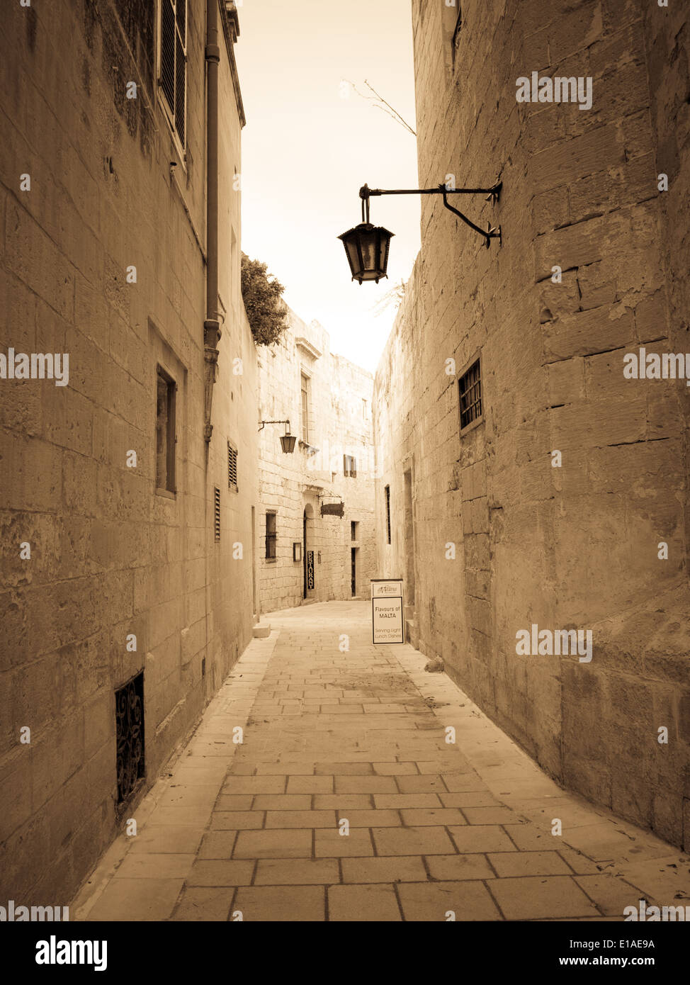 A monotone, sepia view of a narrow medieval street in Mdina, Malta. Malta's old capital, Mdina is also known as Stock Photo