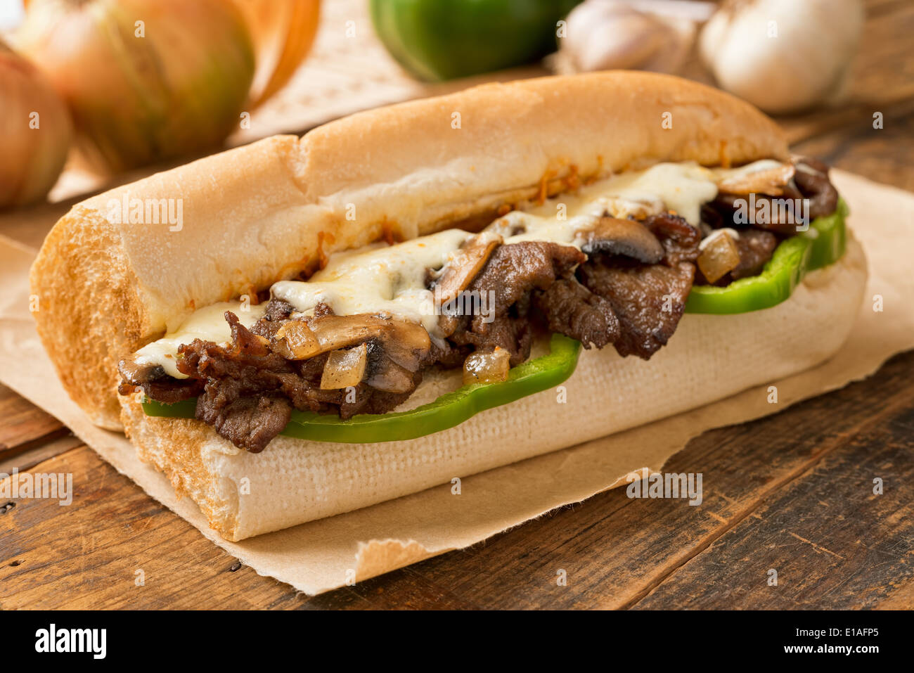 A delicious oven bake steak and cheese submarine sandwich with mushrooms, green peppers, and onion. - Stock Image