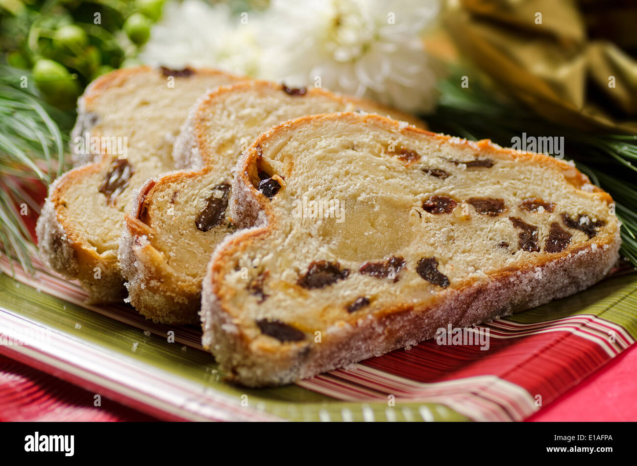 A traditional stollen fruit cake with raisins and marzipan center. - Stock Image