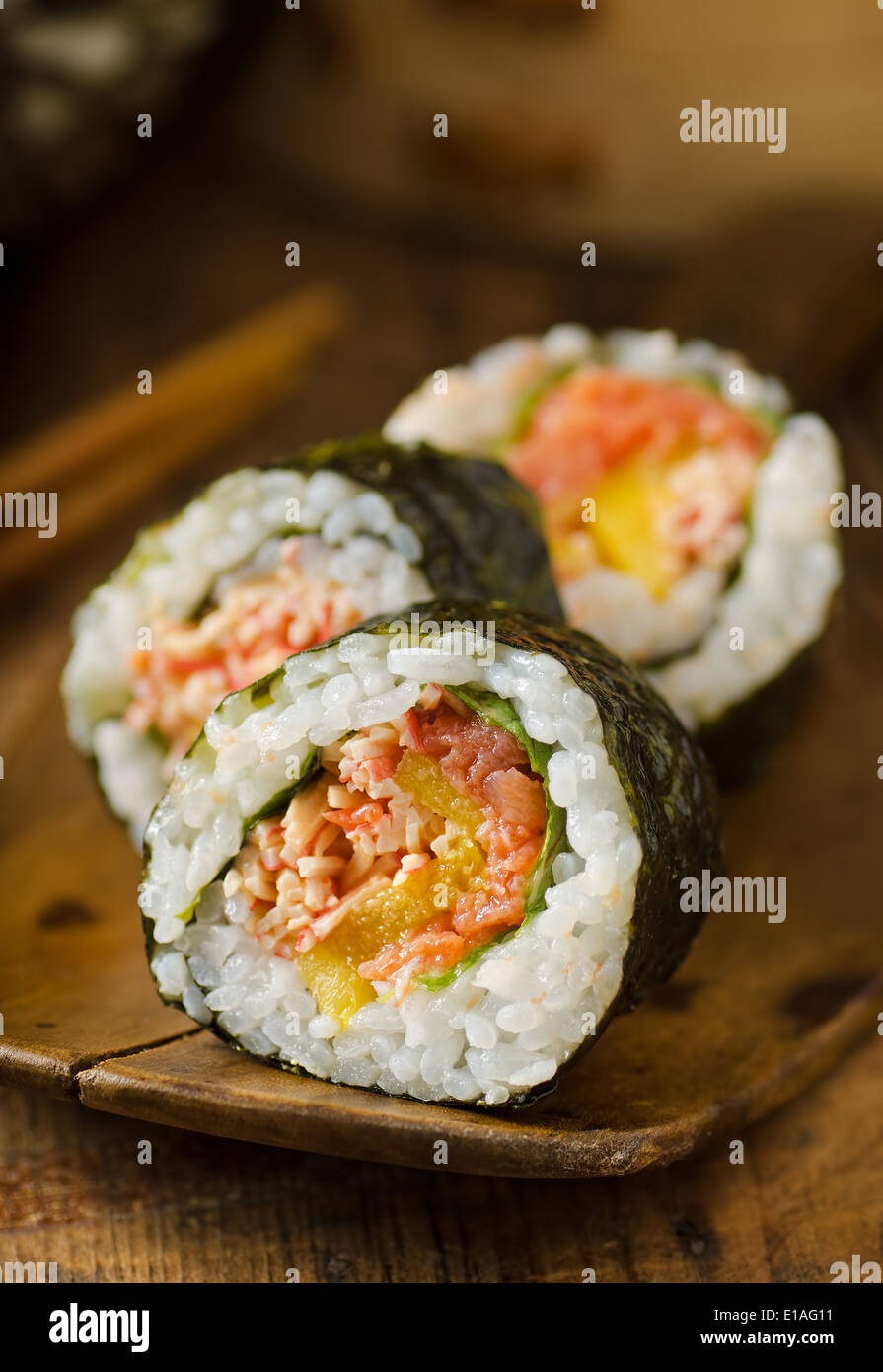 A Japanese sushi roll with smoked salmon and mango. - Stock Image