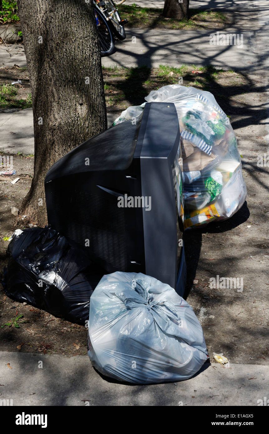 A TV thrown out with the garbage - Stock Image