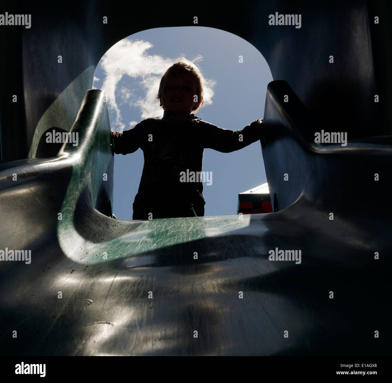 A silhouette of a two year old boy at the top of a slide - Stock Image