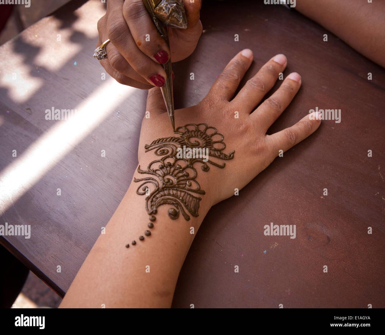 Woman getting henna design on hand - Stock Image