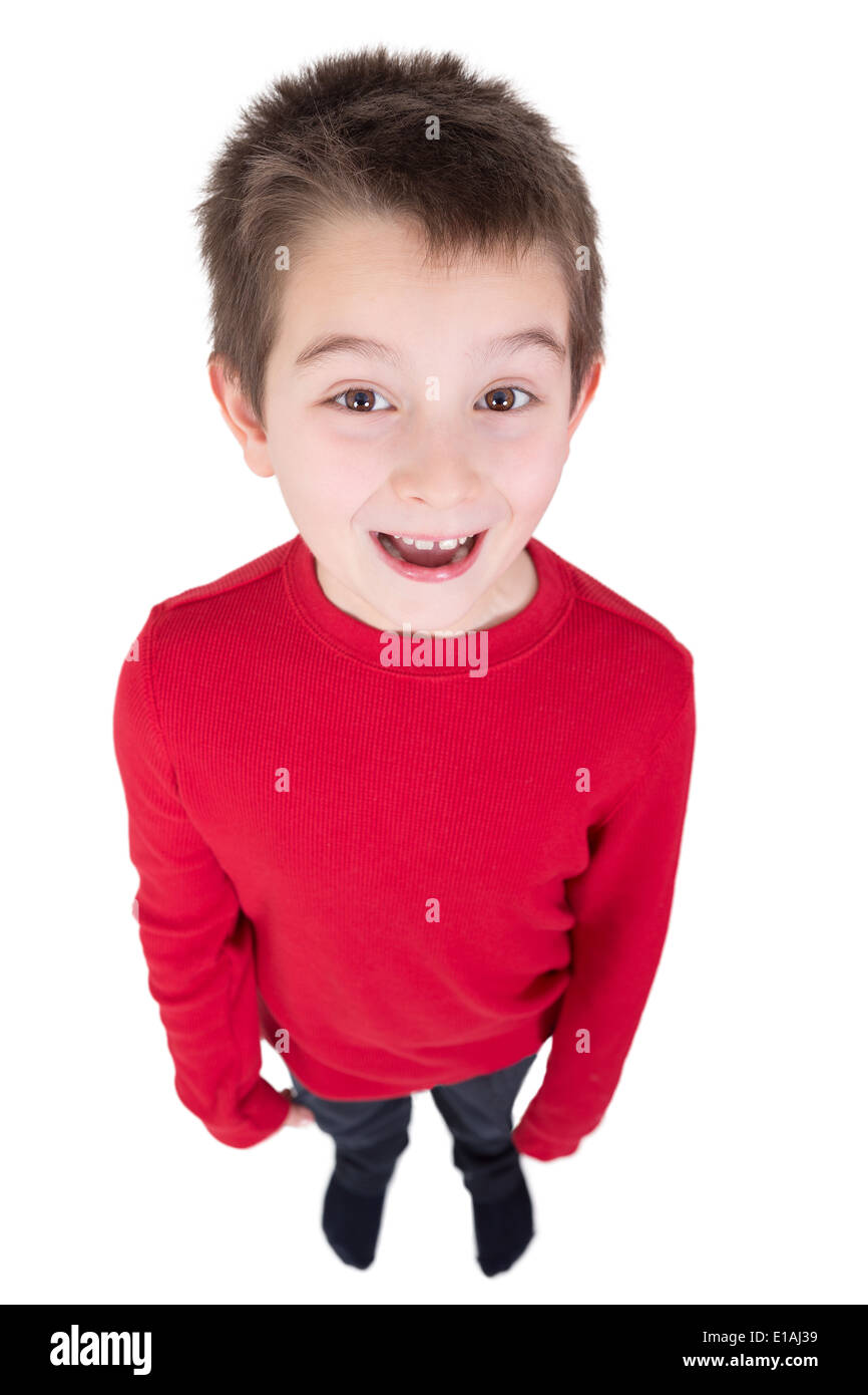 Fun portrait of a laughing young boy looking up at the camera taken full length from a high angle perspective isolated on white - Stock Image