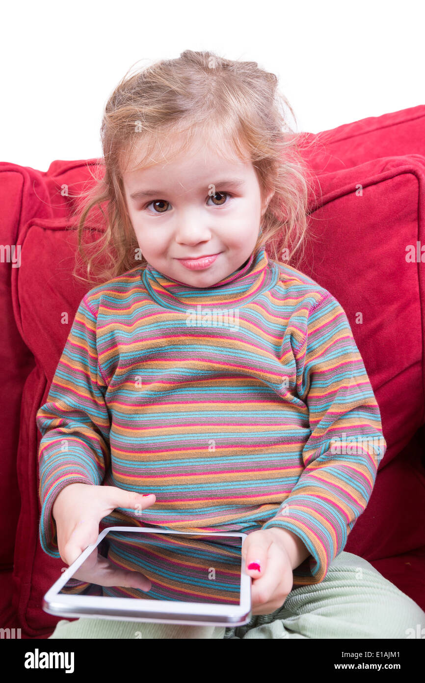 Beautiful toddler with tousled hair and an adorable smile sitting on a red sofa a tablet computer in her hands as she amuses her - Stock Image