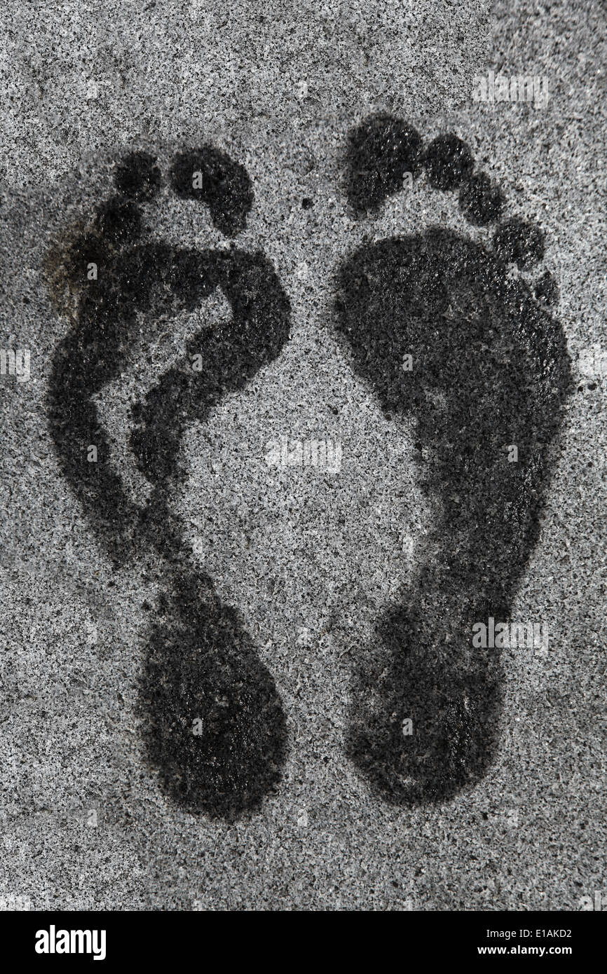 It's a photo of a foot print on the floor view form the top or top view. It's both feet of a man or woman that stand still there - Stock Image