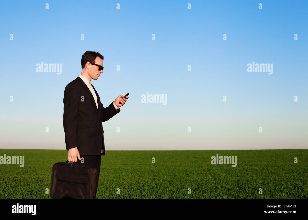 businessman with smartphone in green field - Stock Image