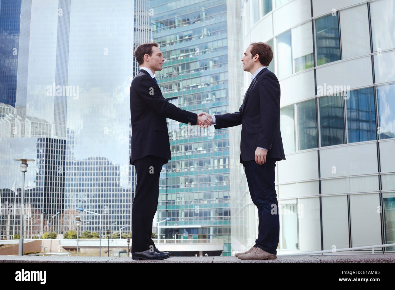 partnership, two businessman on office buildings background - Stock Image
