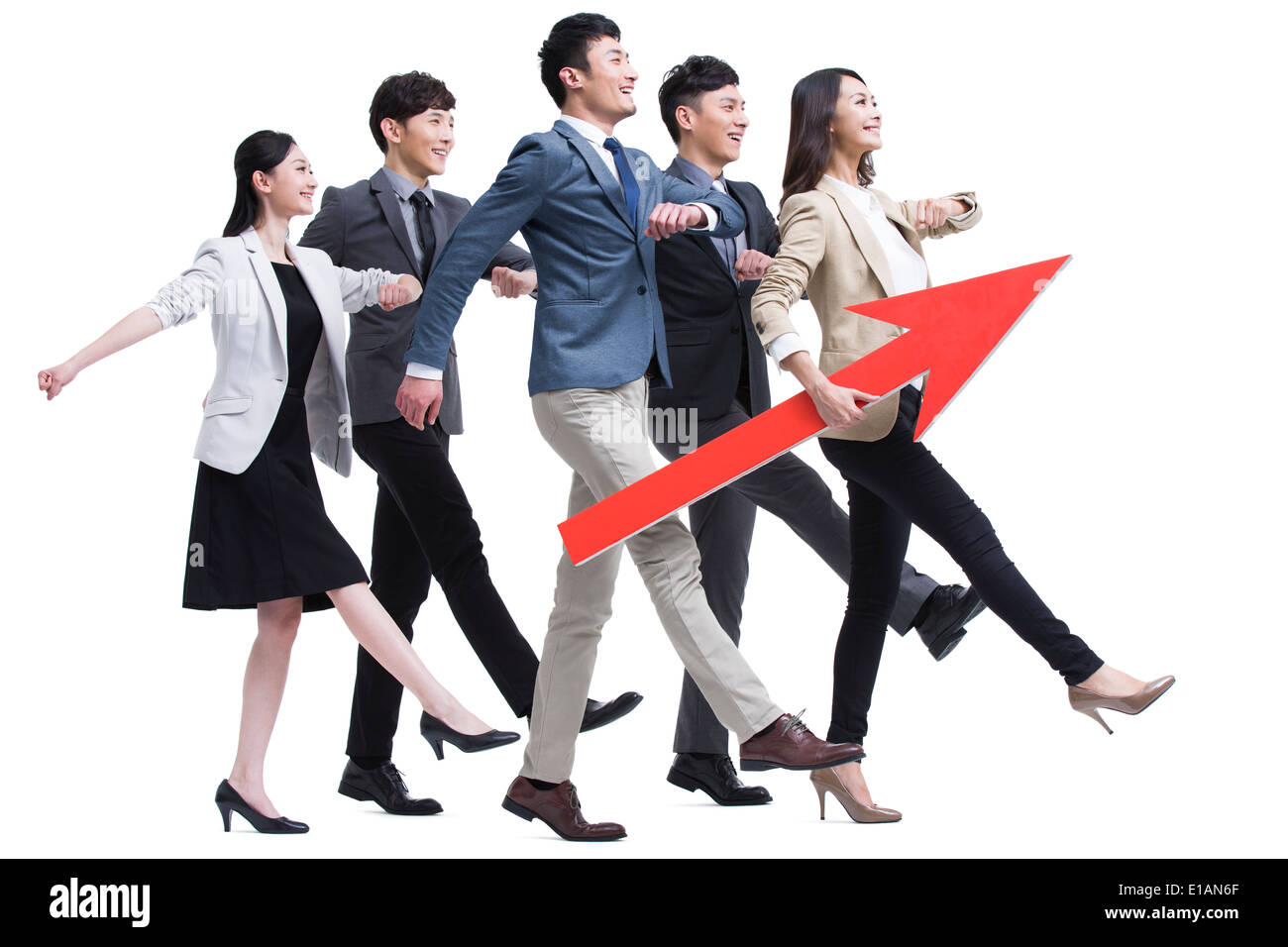 Young businessperson stepping forward with red arrow sign - Stock Image