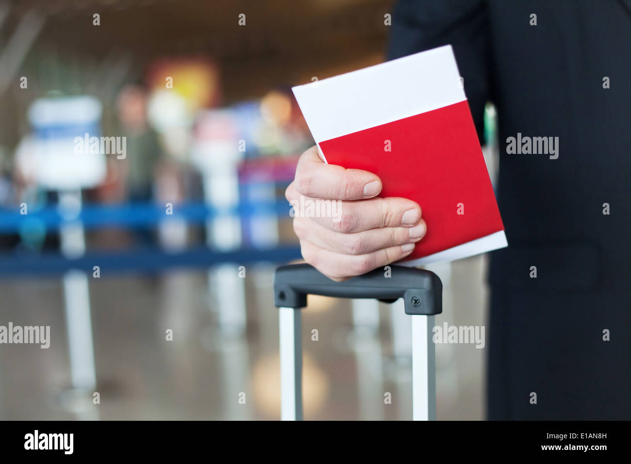 close up of passport and ticket in hand in airport - Stock Image