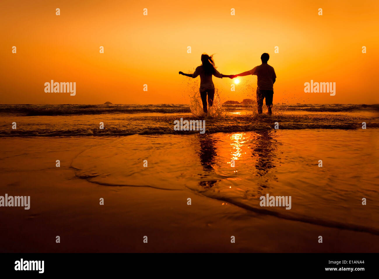 silhouettes of couple running to the sea on the beach at sunset - Stock Image