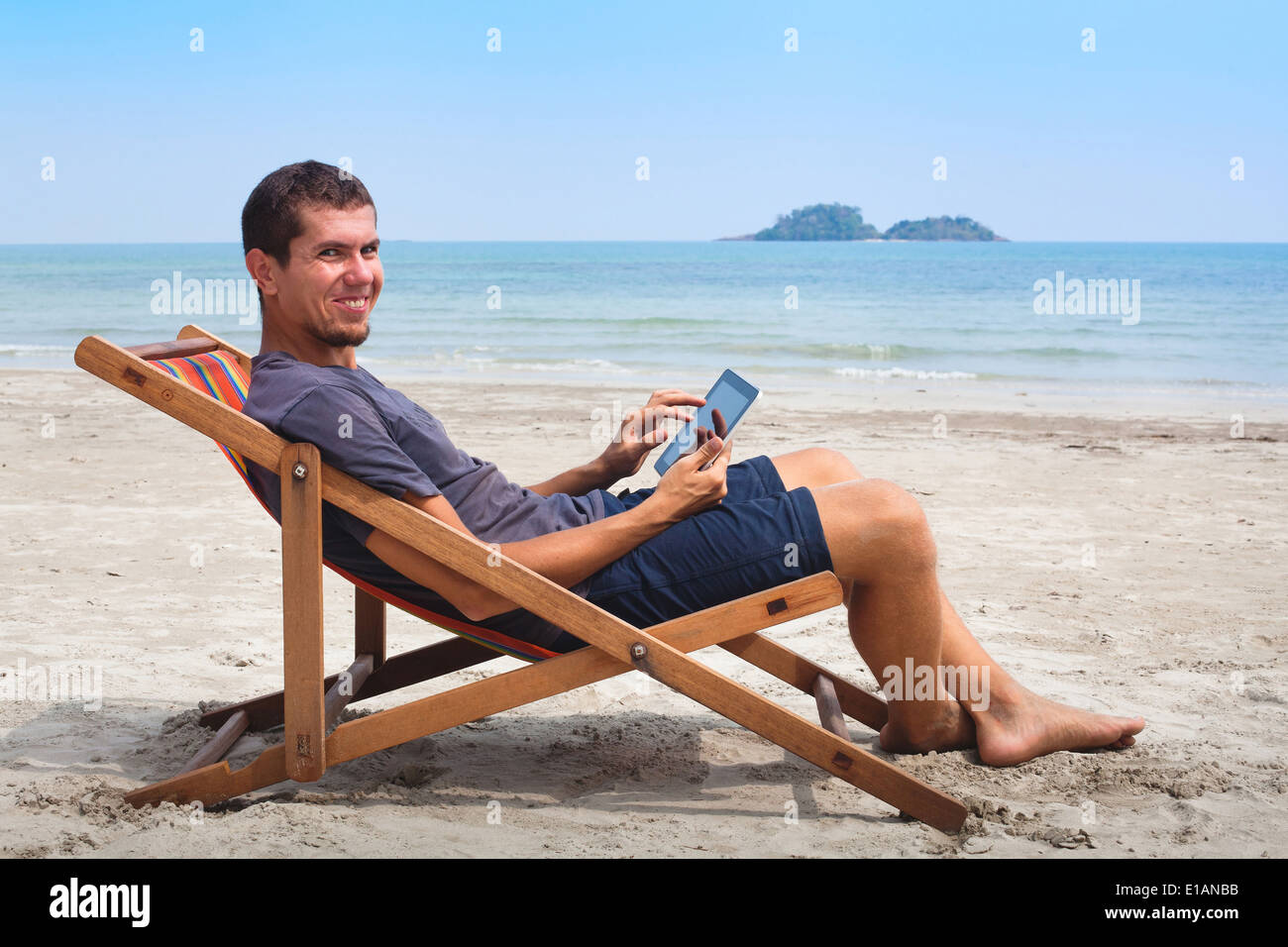 banking online, portrait of happy business man with tablet on the beach - Stock Image