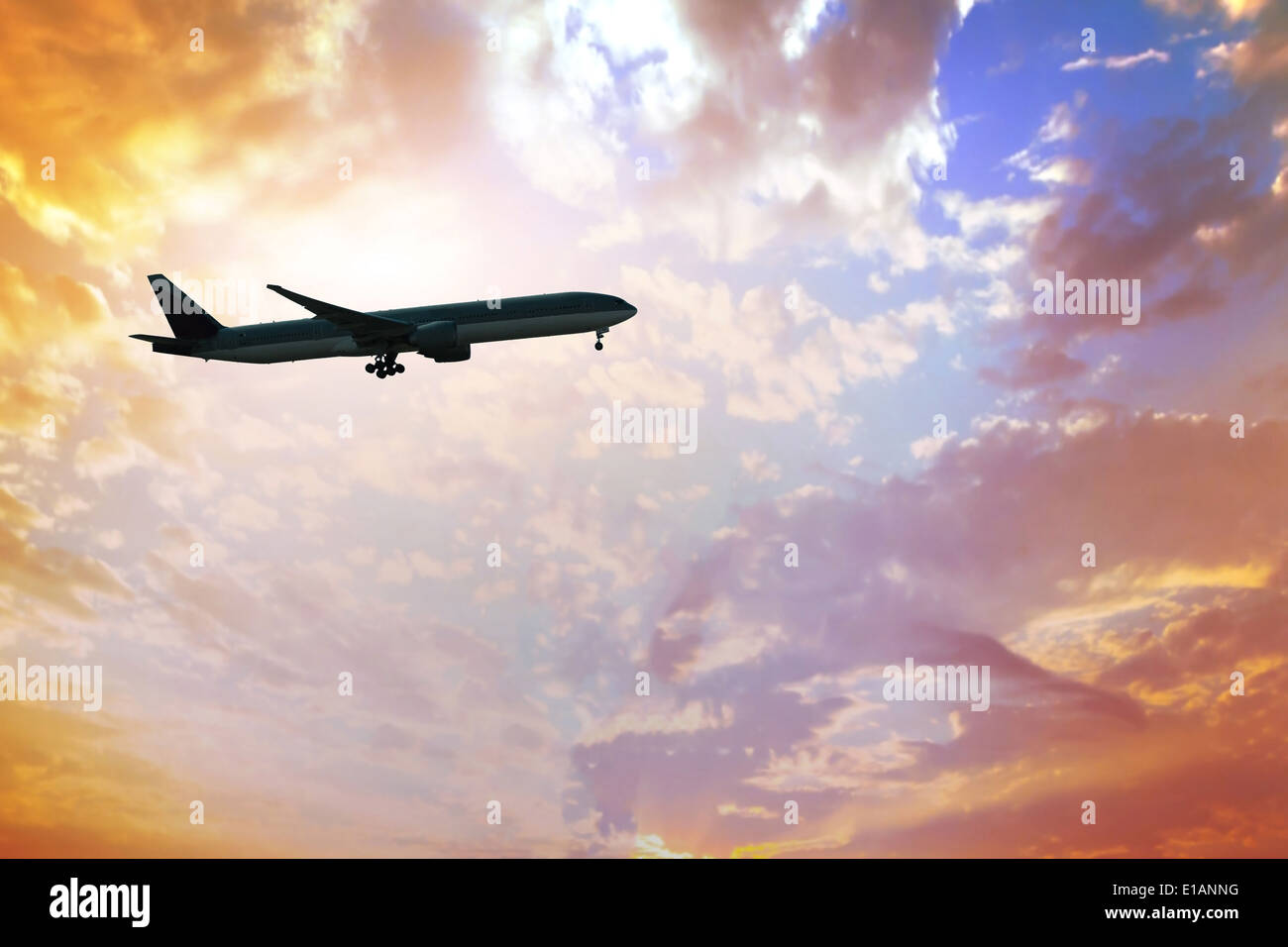 silhouette of airplane at sunset sky - Stock Image