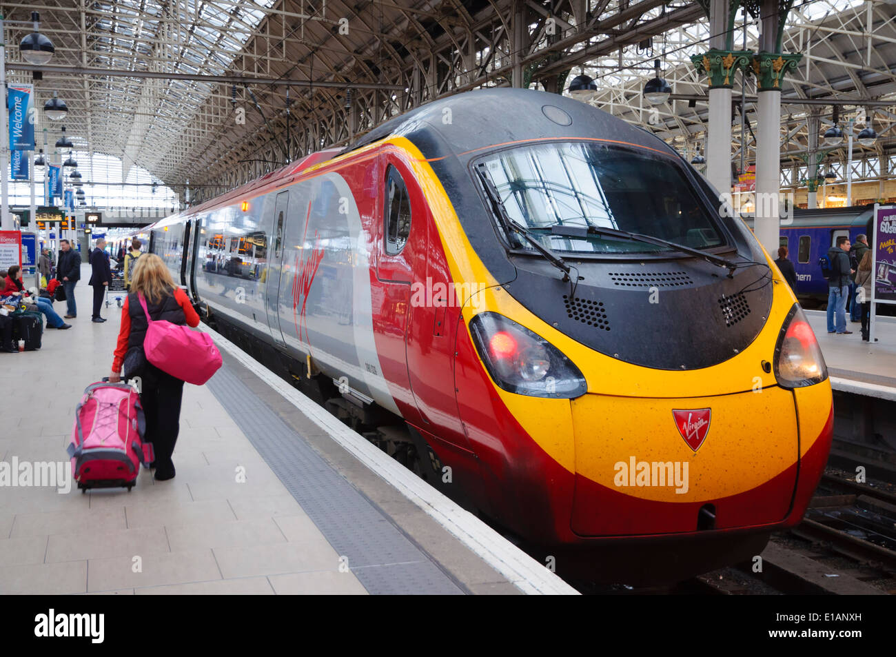 Lady passenger walking on platform with luggage to the Virgin Pendolino train at Manchester Piccadilly Station; Stock Photo