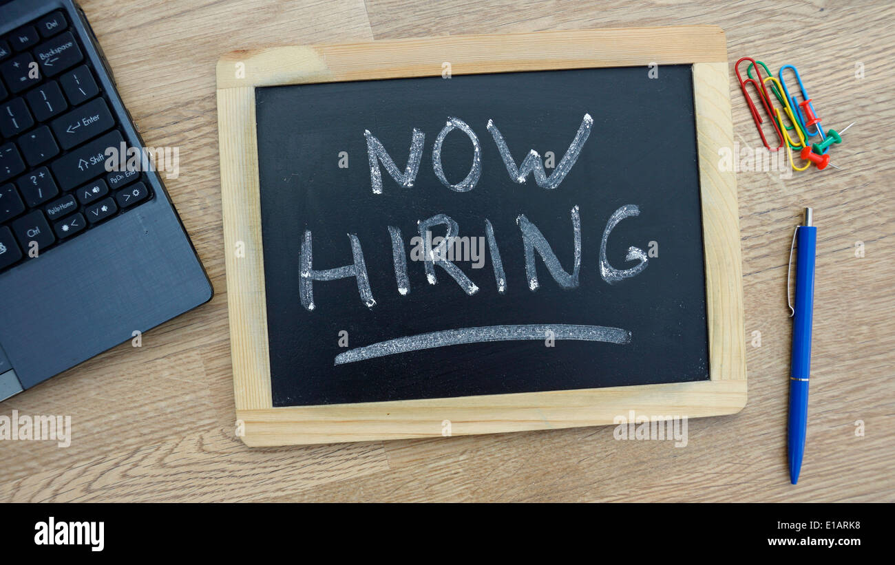 Now hiring written on a chalkboard at the office - Stock Image