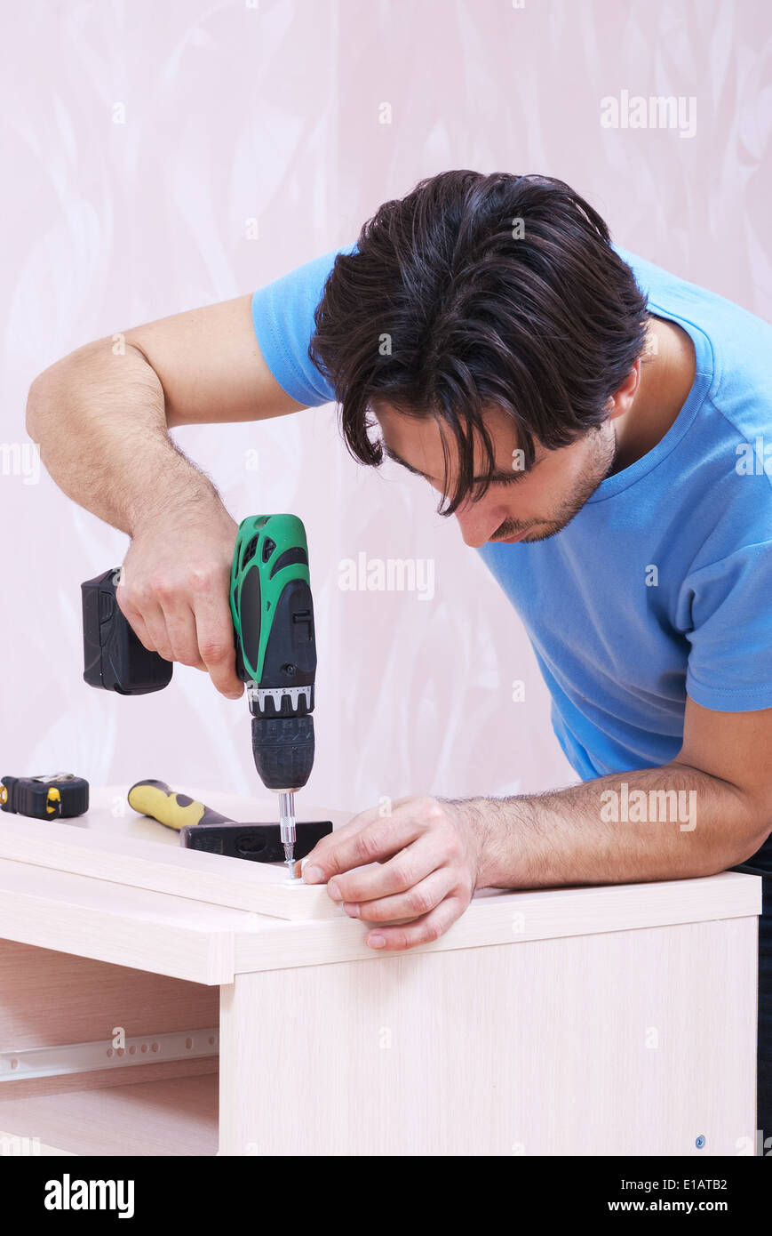 Carpenter collects wood furniture with a drill - Stock Image
