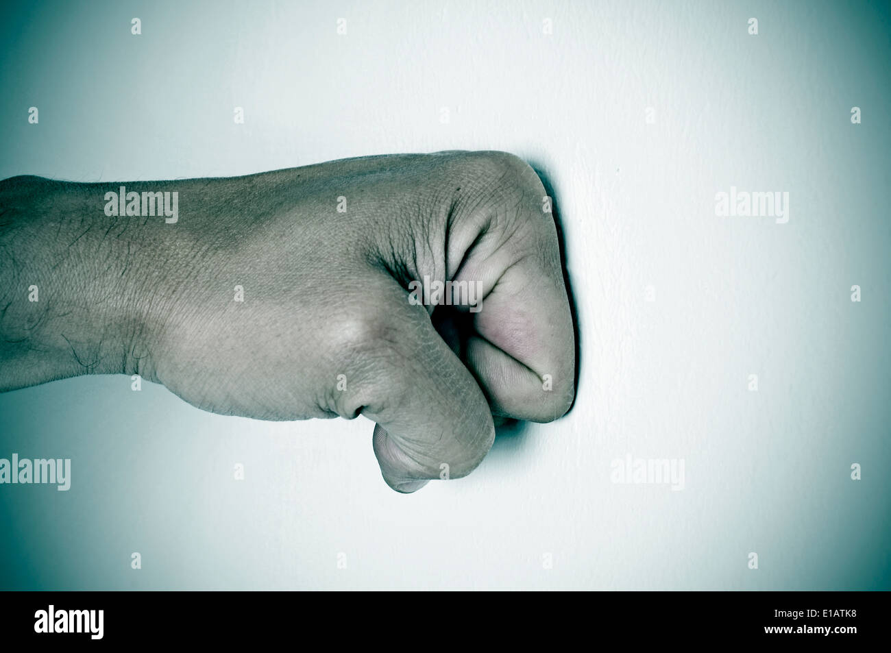 man fist punching a white surface - Stock Image