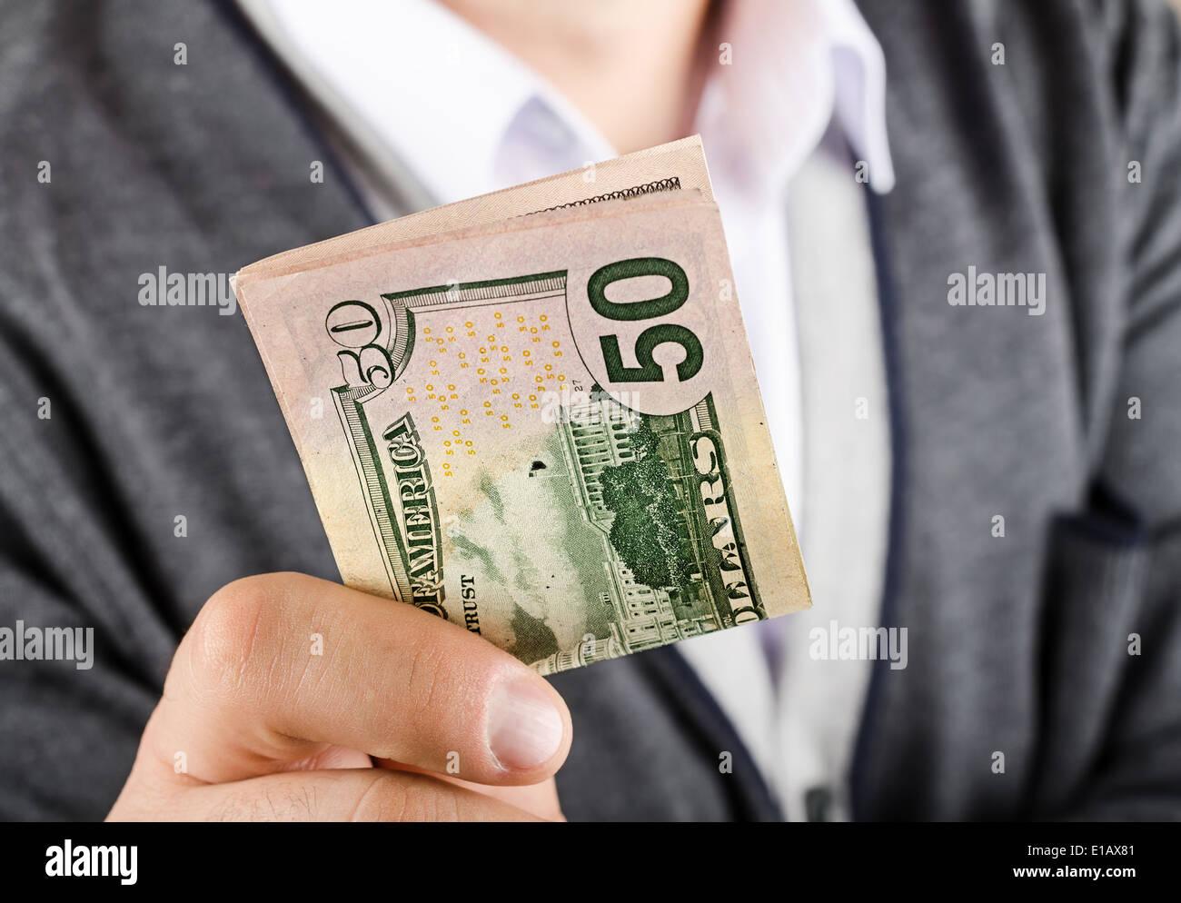 Businessman gives fifty dollars, closeup - Stock Image