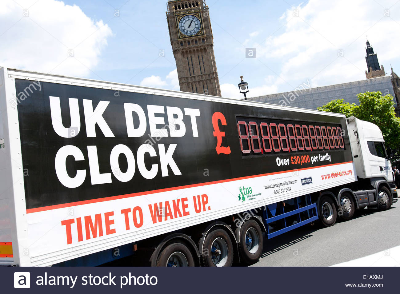 UK, London : UK debt clock lorry passes The Houses of Parliament in London to highlight the UK's national debt. 26.06.2010. - Stock Image