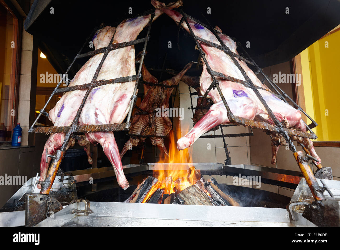 argentine asado whole lamb roasting over burning open fire in restaurant window Ushuaia Argentina - Stock Image