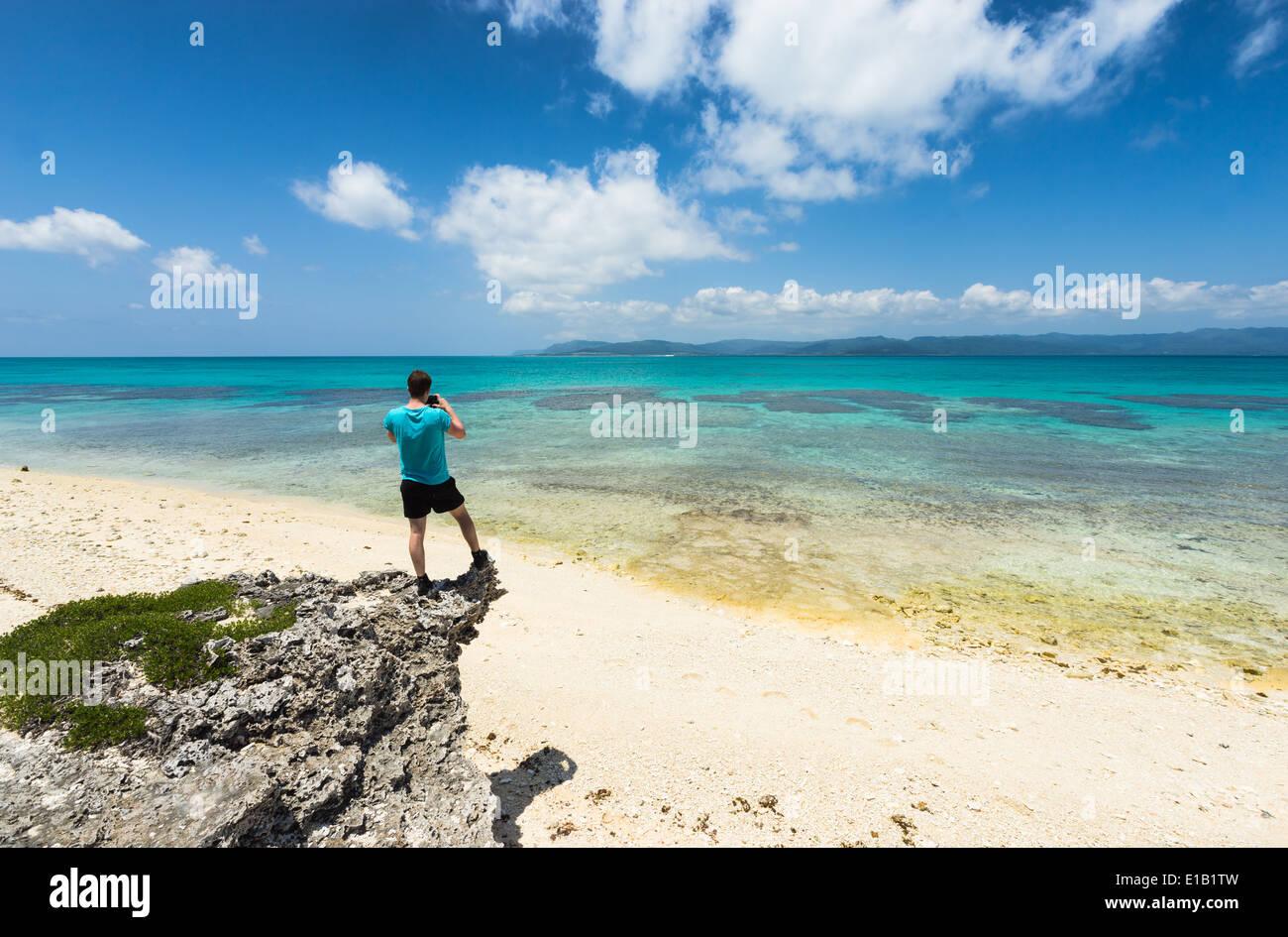 Man taking photo of stunning white sand tropical beach full of healthy coral, Yaeyama islands, Okinawa, Japan - Stock Image