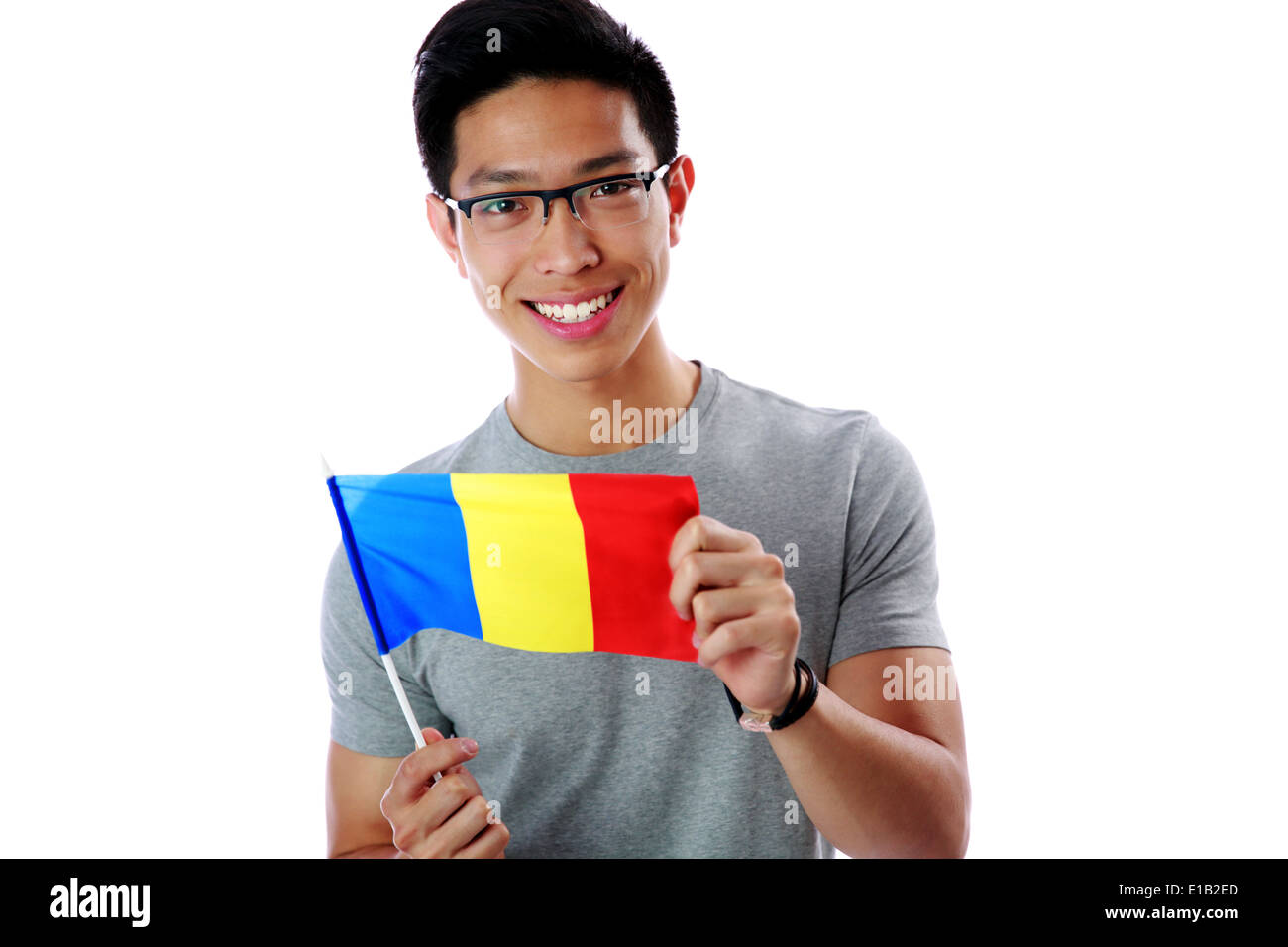 Happy young asian man holding flag of Romania isolated on white background - Stock Image