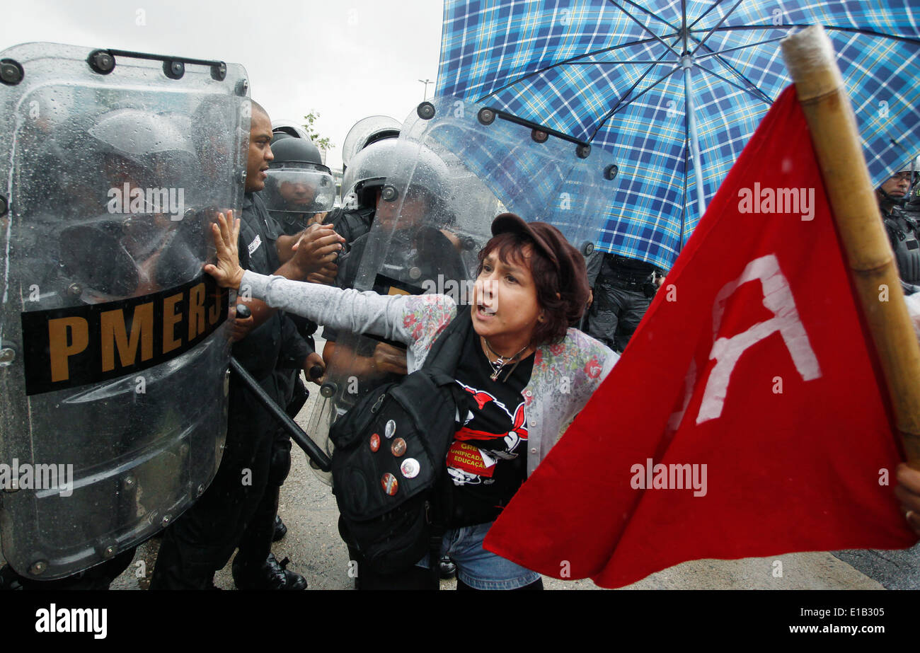 Rio de Janeiro, Brazil- May 28,2014- A teacher on strike fights with anti- riot police agents during a demonstration - Stock Image